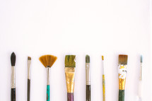 Paintbrushes lined up on a white background.