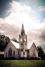 a white church with white clouds