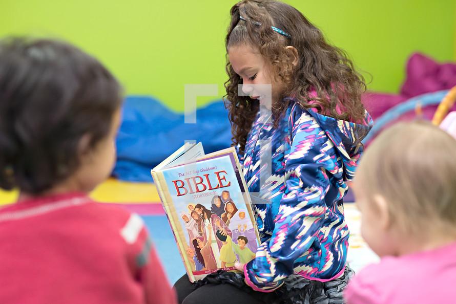 a little girl reading a children's Bible
