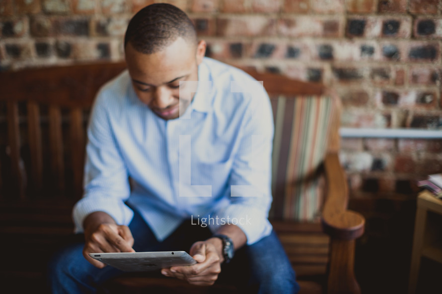 Man reading the Bible on an electronic tablet.