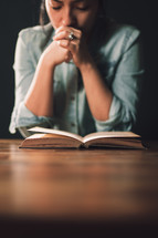 woman praying over a book