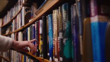 a girl grabbing a Bible off the shelf in a library