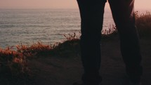 Man standing at cliff overlooking ocean during sunset