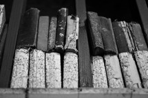 old tattered books on the top shelf of a book shelf