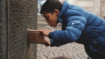 a child drinking from a water fountain