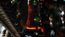 Aerial Top-down pedestal of groups of people hanging out at  night on a rooftop poolside lounge with DJ