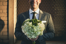 groom holding bridal bouquet
