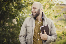man holding a Bible outdoors