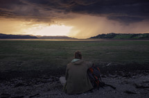 man with a backpack looking out over a grassy area along a shore at sunset