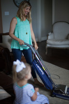 a woman vacuuming while her toddler daughter watches tv