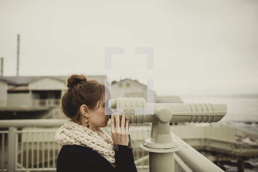 woman looking through a telescopic viewfinder