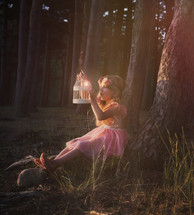 a child holding a fairy in a cage in the woods