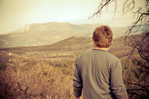Man looking at a mountian range.