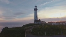 a lighthouse and coastline | direction | aerial | flight | motion