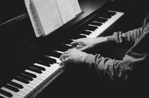 A man plays  chord on a piano