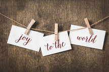 word joy to the world on card stock hanging on twine by a clothespin
