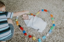 a big brother making a heart around his baby sister with legos
