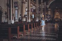 a woman walking down the aisle of a Catholic church