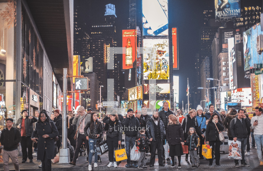 crowds of shoppers waiting at a crosswalk in a city at night