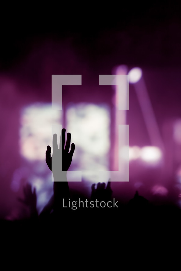 purple stage lights and silhouettes of raised hands at a concert
