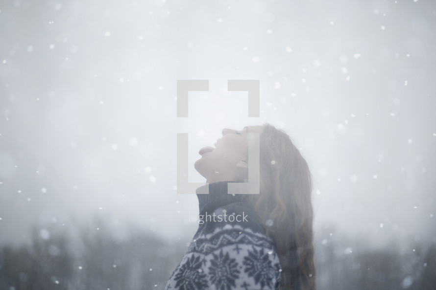 a woman catching snowflakes on her tongue