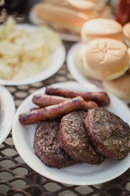 hamburgers and hotdogs on a table outdoors