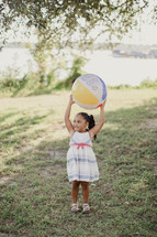 A little girl holding a beach ball over her head.