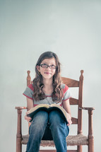 Girl sitting in a chair reading her bible - with a facial impression of thinking something nice.