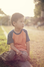 boy child sitting in the grass