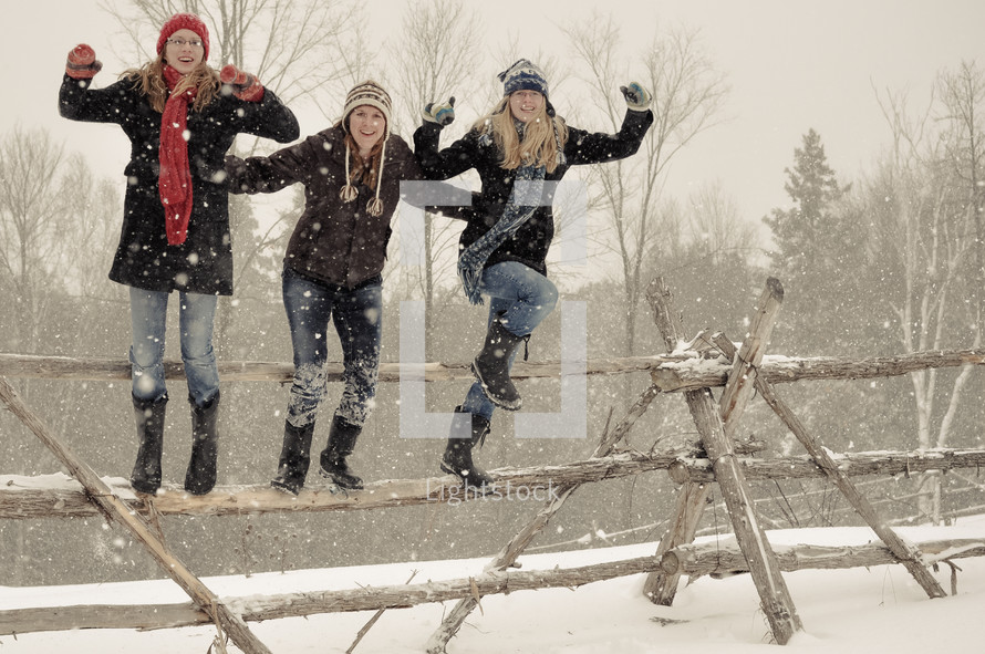 teen girls jumping off a fence in snow