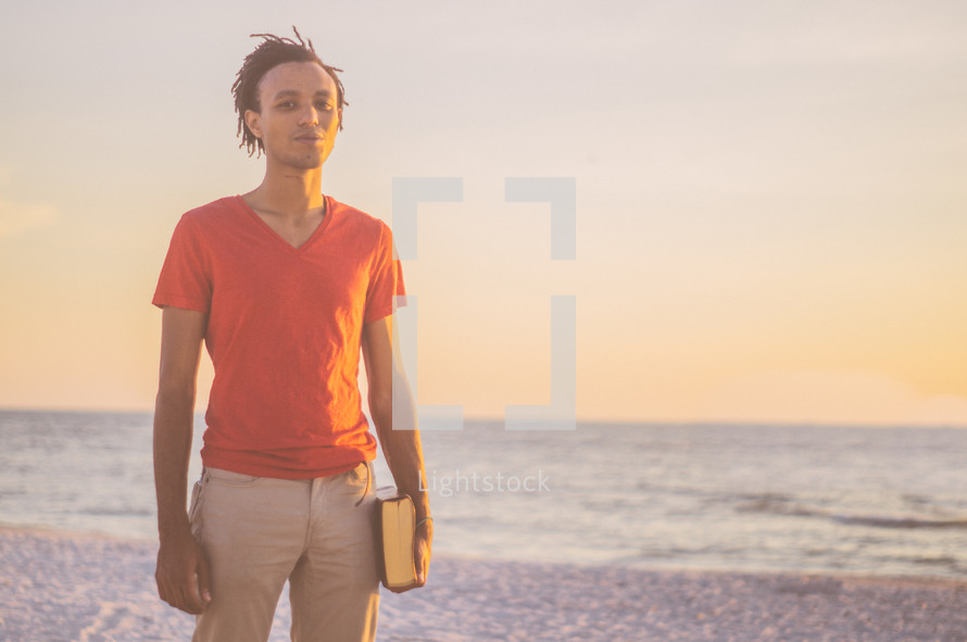 African-American man standing on a beach at sunset holding a Bible