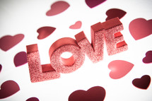 the word LOVE in red glitter Letters and red hearts