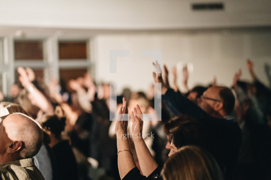 parishioners with hands raised during a worship service