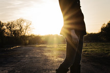 a torso of a woman standing on a dirt road in a sun flare