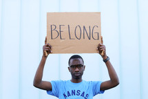 A man holding up a BELONG sign