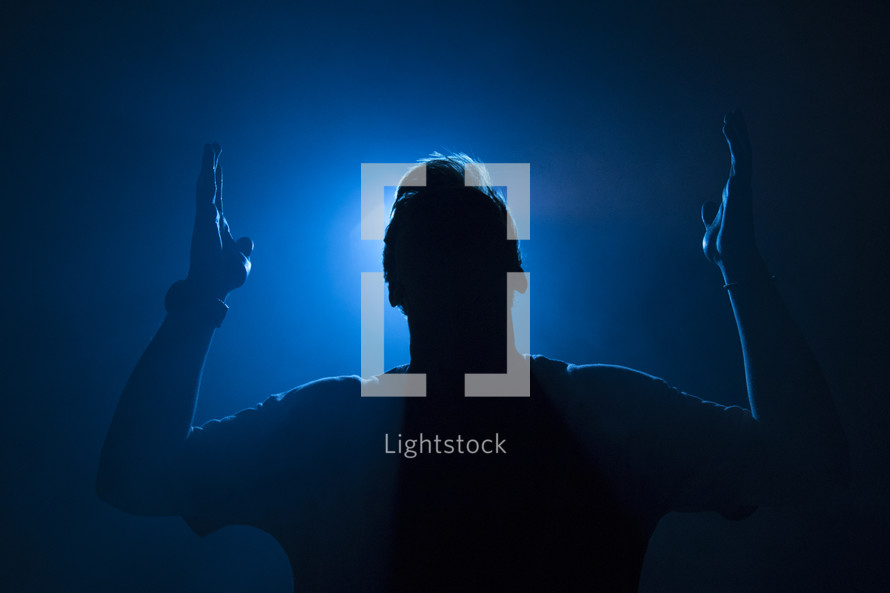 a man with hands raised illuminated in darkness