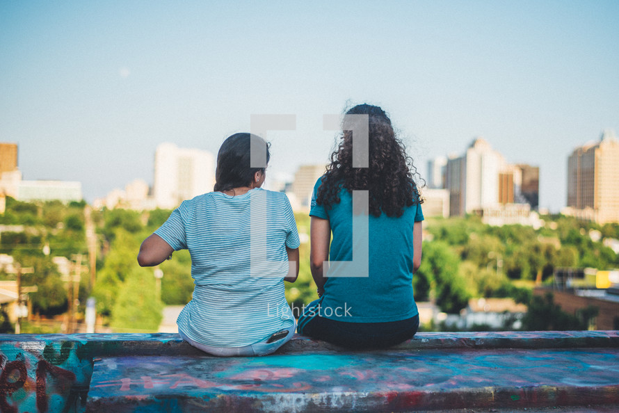 girls sitting on a rooftop looking out at a city