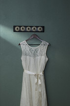 a wedding dress hanging on a hook