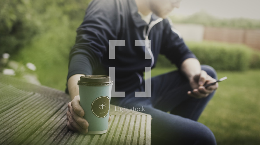 a man texting with his hand on a coffee cup