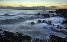 waves along a rocky shore at sunset