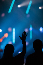 silhouette of a woman with her hands raised to God at a worship service