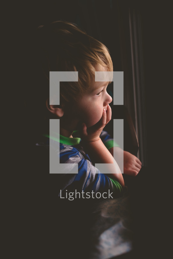 a toddler boy looking out a window