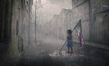 A little girl holds an American flag that is melting in the rain storm