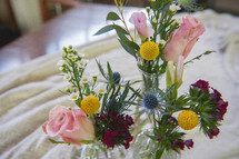 flowers in vases on a tablecloth