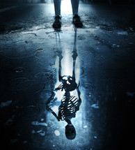 The figure of a skeleton forms in a puddle on a city sidewalk.
