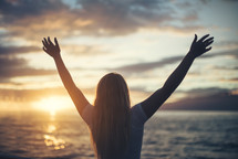 woman standing on a beach with hands raised in praise