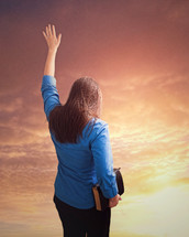 Woman holding a bible with arm raised under and orange sky.