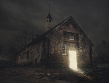 a light glowing in the doorway of an abandoned church