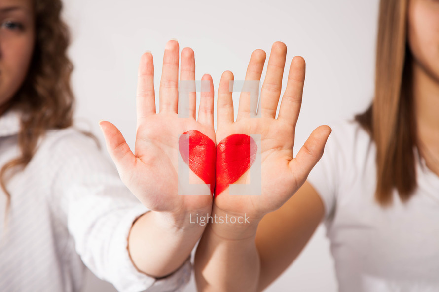 Two girls hands pressed together to form a heart.