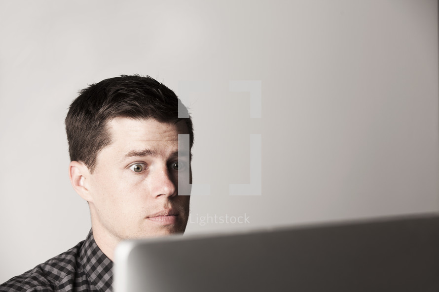 Wide-eyed man looking at a laptop screen.